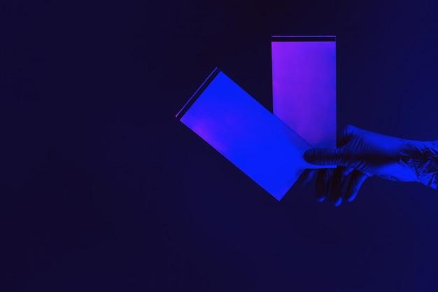 Teruggave van twee tickets. dien medische handschoen tegen een donkere achtergrond in