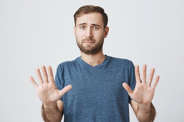 Terughoudend man handen schudden in weigering, aanbod afwijzen