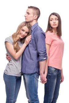 Terwijl de man een meisje knuffelt, houdt hij de hand van een ander vast.