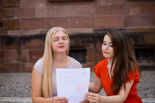 Test mislukt. bezorgde en droevige vrouwelijke studentenzitting met definitief testresultaat