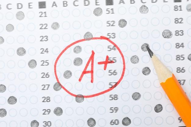 Test scoreblad met antwoorden, cijfer a + en potlood, close-up