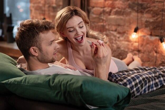 Test van geliefde. bebaarde man kijkt naar positieve zwangerschapstest van zijn geliefde terwijl hij samen in bed ligt