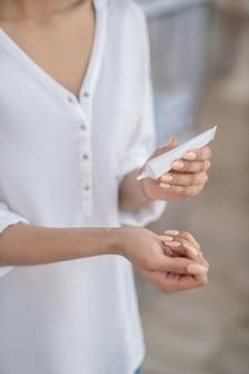 Testen, verzorgingsproduct. close-up van vrouwelijke handen en cosmetisch product op pols en in buis, gezicht niet zichtbaar