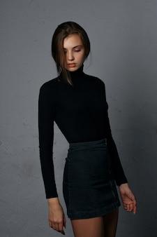 Testopname voor glorieus jong model met spijkerrok en zwarte trui