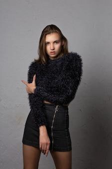 Testopname voor verbluffende jonge vrouw draagt modieuze kleding en poseert in de studio
