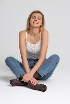 Testopname voor vrolijke jonge vrouw draagt modieuze kleding, poserend in studio