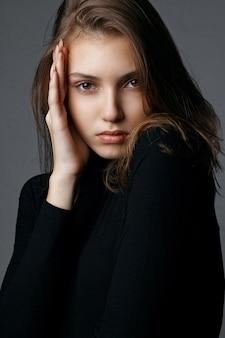 Testopnamen voor glorieus jong model met natuurlijke make-up met zwarte trui. close-up shot