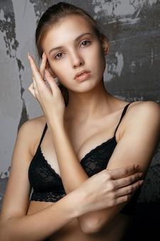 Testopnames voor een prachtig jong meisje met natuurlijke make-up die een zwarte kanten beha draagt. close-up shot