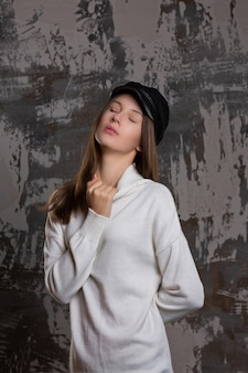 Testshoot van sensuele brunette vrouw poseren in stijlvolle pet en gebreide jurk