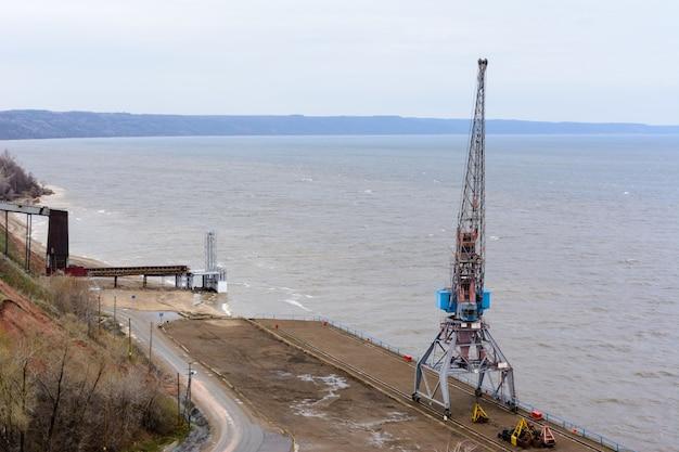 Tetyushi, tatarstan / rusland - 2 mei 2019: bovenaanzicht van de lege industriële pier met vrachthavenkraan op het dok langs de ruime wolga. binnenvaart wordt niet geclaimd en niet gebruikt.
