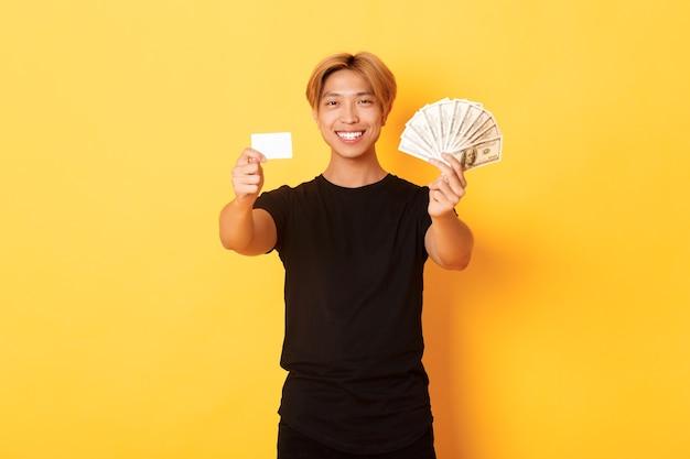 Tevreden aantrekkelijke koreaanse kerel met blond haar, die geld en creditcard toont, gelukkige, gele muur glimlacht