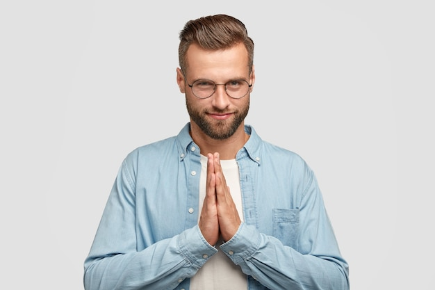 Tevreden aantrekkelijke ongeschoren man houdt handen in gebed gebaar, gelooft in geluk, heeft zelfverzekerde uitdrukking, draagt een ronde bril, heeft trendy kapsel, poseert binnen. mensen en geloofsconcept