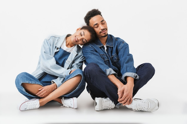 Tevreden afrikaanse paar in denim shirts zitten samen op de vloer met gesloten ogen over grijze muur