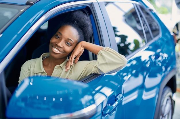 Tevreden afrikaanse vrouw achter het stuur van blauwe auto vertegenwoordigd in auto showroom