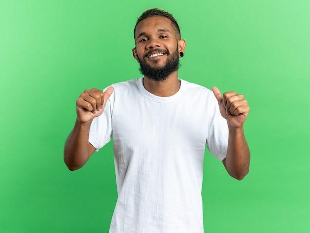 Tevreden afro-amerikaanse jongeman in wit t-shirt glimlachend zelfverzekerd wijzend naar zichzelf terwijl hij over groen staat