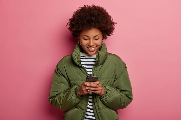 Tevreden afro-amerikaanse tiener houdt mobiele telefoon vast, gericht naar beneden in scherm, draagt zeeman trui en winterjas, controleert inkomstenbericht, bekijkt video online tijdens de vrije tijd