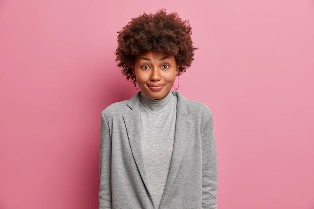 Tevreden afro-amerikaanse vrouw in grijze formele kleding voelt zich gelukkig