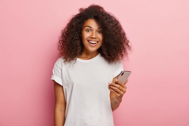 Tevreden afro-amerikaanse vrouw in vrijetijdskleding, houdt moderne smartphone vast, wacht op oproep, blij bericht van vriend te ontvangen