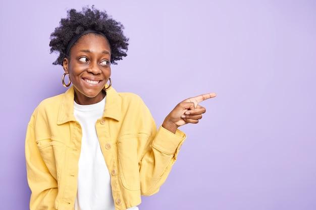 Tevreden afro-amerikaanse vrouw met donker krullend haar glimlacht aangenaam en wijst weg rechts toont kopieerruimte