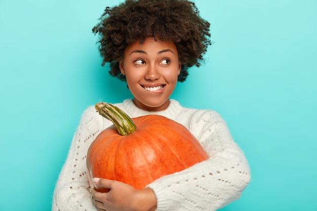 Tevreden afro-meisje omarmt grote oranje pompoen, bijt lippen, draagt gebreide witte trui, heeft herfststemming, kijkt opzij, geïsoleerd op blauwe achtergrond.