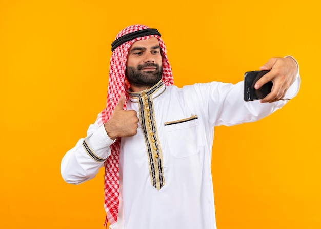 Tevreden arabische zakenman in traditionele slijtage die selfie met zijn smartphone neemt die zelfverzekerd over oranje muur kijkt