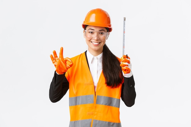 Tevreden aziatische vrouwelijke bouwingenieur, architect of inspecteur bij onderneming die goed gebaar en meetlint toont, tevreden glimlacht, toestemming geeft, metingen goedkeurt zijn geldig