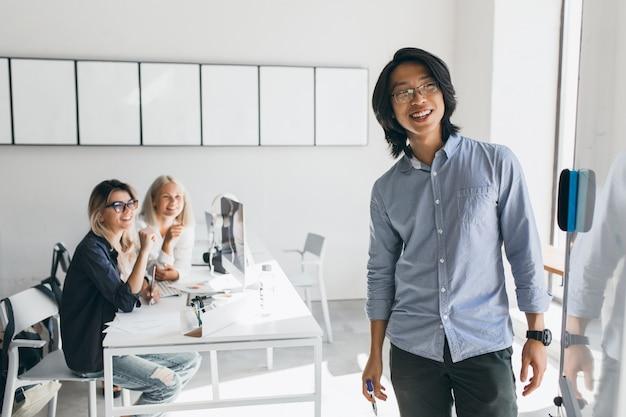 Tevreden aziatische zakenman die flip-over met glimlach bekijkt die zich in conferentiezaal bevindt. charmante blonde vrouwelijke studenten met laptops kijken naar jonge leraar schrijven aan boord.