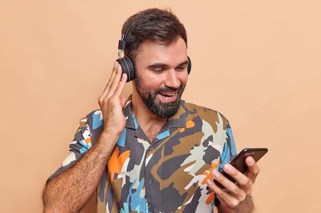 Tevreden bebaarde man controleert geluid in draadloze stereo hoofdtelefoon