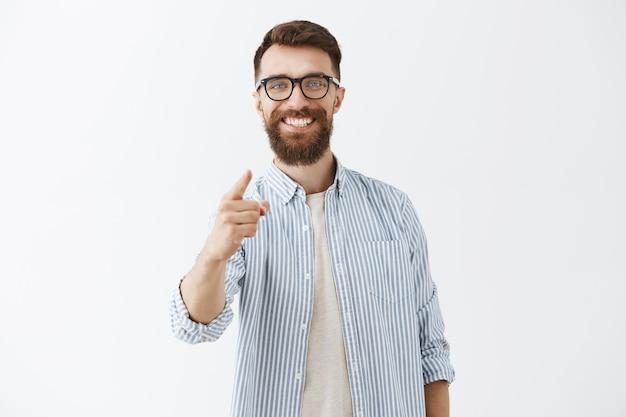 Tevreden bebaarde man die tegen de witte muur poseert