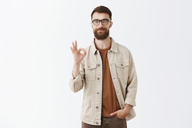 Tevreden bebaarde man in glazen poseren tegen de witte muur