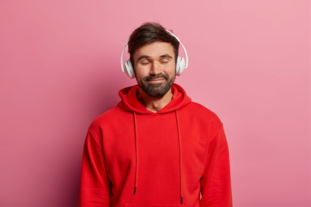 Tevreden, bebaarde man luistert graag naar muziek in een stereohoofdtelefoon, sluit de ogen en lacht zachtjes, draagt een rood sweatshirt, voelt zich goed, modellen op een roze pastelkleurige muur. tieners, hobby, lifestyle-concept