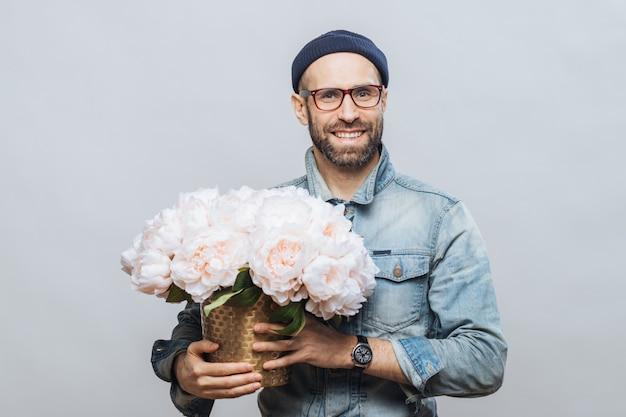 Tevreden bebaarde man met vrolijke uitdrukking heeft brede glimlach, houdt bos bloemen vast