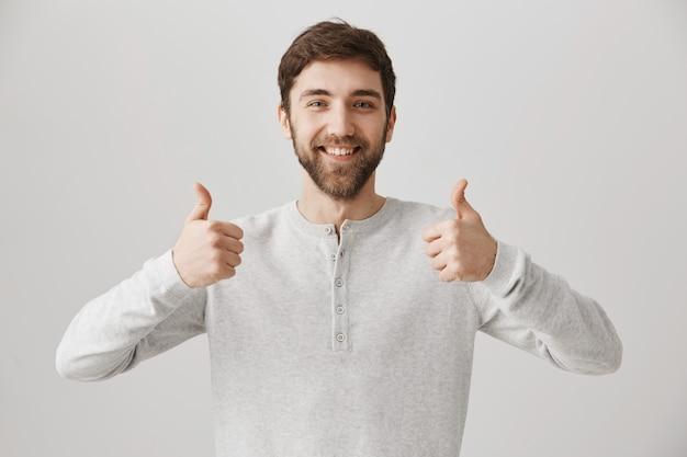 Tevreden, bebaarde mannelijke klant toont goedkeuring met duim omhoog