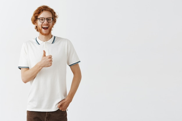 Tevreden bebaarde roodharige man poseren tegen de witte muur met een bril