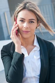 Tevreden bedrijfsvrouw die op smartphone in openlucht spreekt