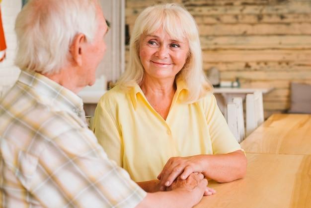 Tevreden bejaarde echtpaarzitting in koffie en hand in hand
