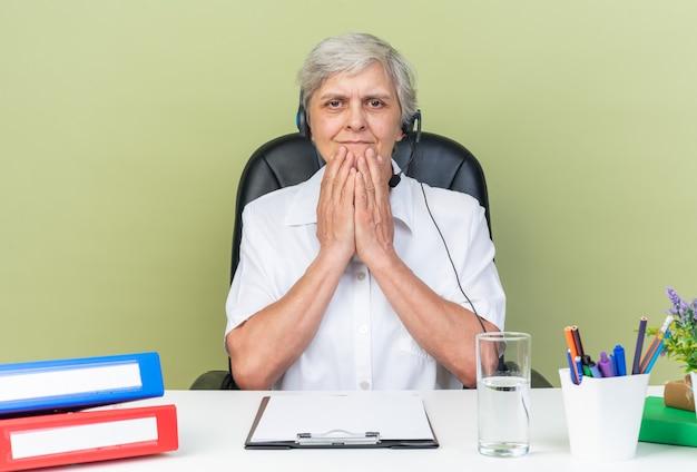 Tevreden blanke vrouwelijke callcenter-operator op een koptelefoon die aan het bureau zit met kantoorhulpmiddelen die handen op haar kin leggen