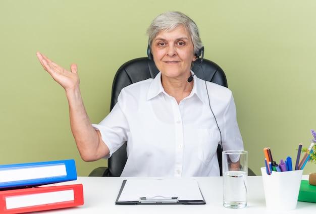 Tevreden blanke vrouwelijke callcenter-operator op koptelefoon zittend aan bureau met kantoorhulpmiddelen die haar hand open houden