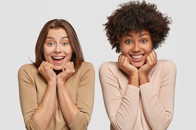 Tevreden blije vrouwen van gemengd ras hebben blije uitdrukkingen, houden de handen onder de kin, uiten positieve emoties