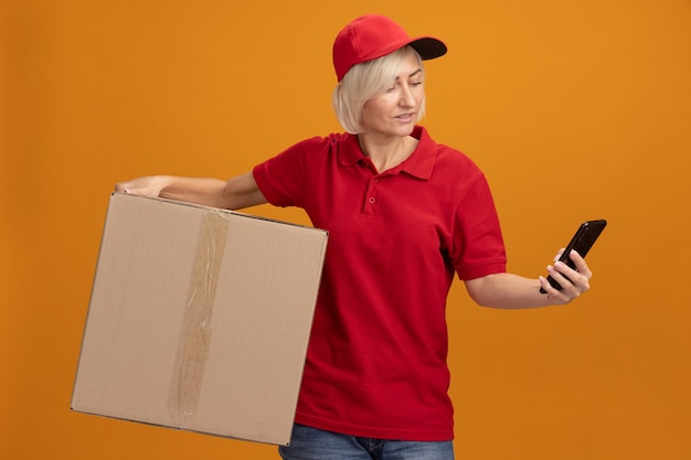 Tevreden blonde bezorger van middelbare leeftijd in een rood uniform en een pet met een kartonnen doos en een mobiele telefoon die naar de telefoon kijkt