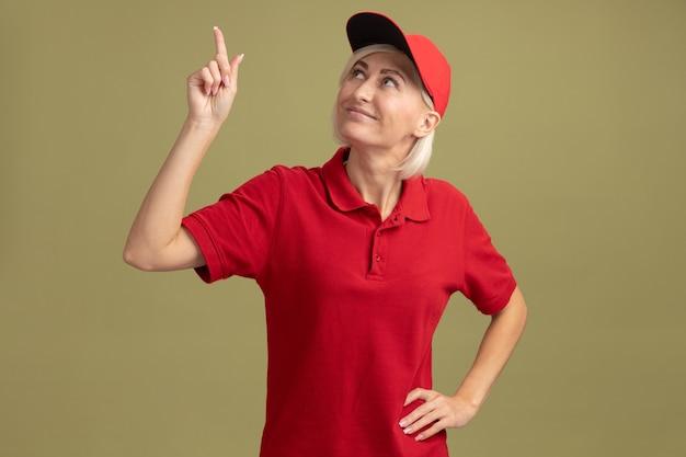 Tevreden blonde bezorger van middelbare leeftijd in rood uniform en pet die de hand op de taille houdt en naar boven wijst