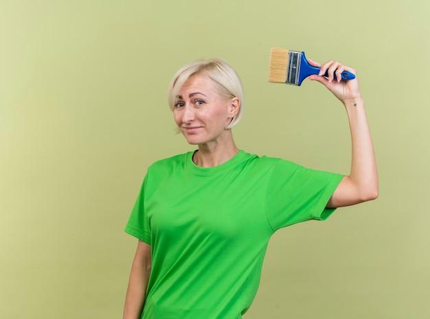 Tevreden blonde slavische vrouw die op middelbare leeftijd camera bekijkt die verfborstel opheft die op olijfgroene achtergrond met exemplaarruimte wordt geïsoleerd