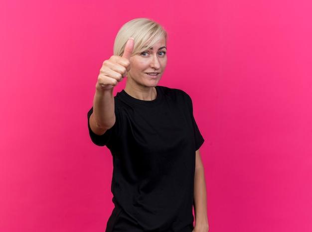 Tevreden blonde slavische vrouw die op middelbare leeftijd duim toont die omhoog op karmozijnrode muur met exemplaarruimte wordt geïsoleerd