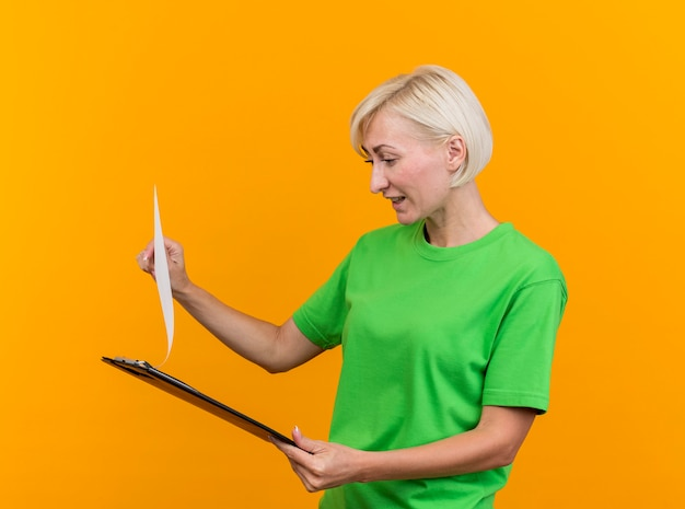 Tevreden blonde slavische vrouw die op middelbare leeftijd houdt en klembord bekijkt dat op gele achtergrond wordt geïsoleerd
