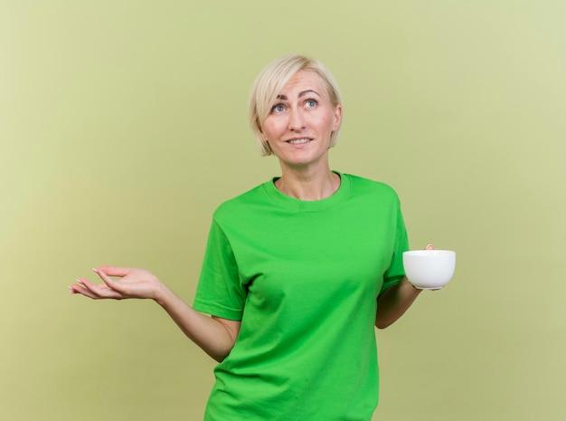 Tevreden blonde slavische vrouw die op middelbare leeftijd kop thee bekijkt die kant bekijkt die lege hand toont die op olijfgroene muur wordt geïsoleerd