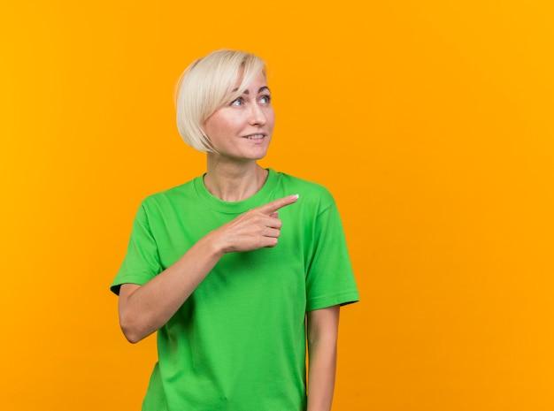 Tevreden blonde slavische vrouw die van middelbare leeftijd kijkt en naar kant kijkt die op gele achtergrond met exemplaarruimte wordt geïsoleerd