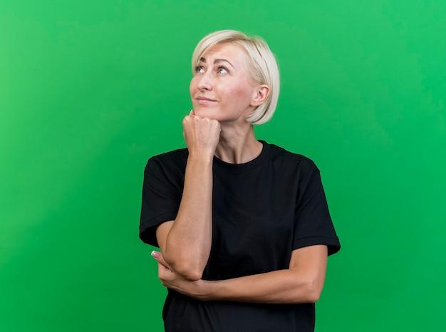 Tevreden blonde slavische vrouw van middelbare leeftijd die hand onder kin zet die kant bekijkt die op groene achtergrond met exemplaarruimte wordt geïsoleerd