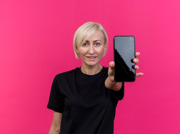 Tevreden blonde slavische vrouw van middelbare leeftijd die zich uit mobiele telefoon uitstrekt naar geïsoleerd op karmozijnrode muur met exemplaarruimte