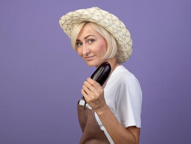 Tevreden blonde tuinmanvrouw van middelbare leeftijd in uniform met hoed