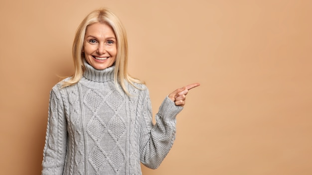 Tevreden blonde vrouw van middelbare leeftijd met rimpels draagt warme grijze trui, wijzend op kopie ruimte